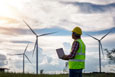 Engineering man standing holding laptop looking wind turbines cl